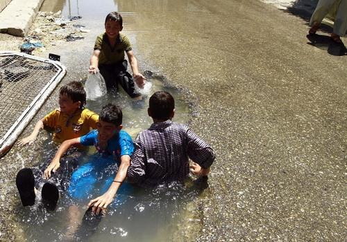آب تنی کردن کودکان حلب در میان جنگ و خون - عکس از حمید خطیب