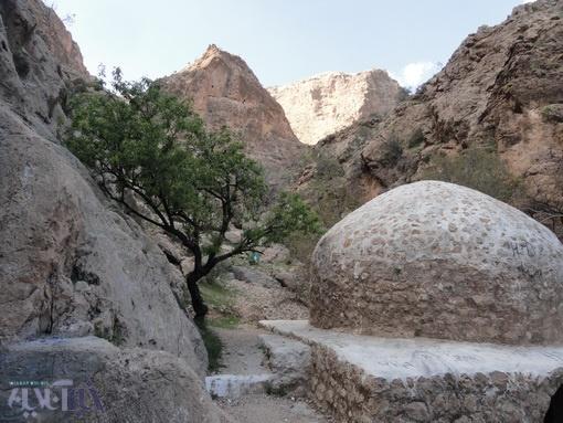 زبالهی آویزان بر درخت بادام در بین مسجد سنگی و گنبد چهار طاقی ایج