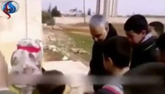 سردار قاسم سلیمانی در حال توزیع شیرینی بین کودکان نبل الزهرا