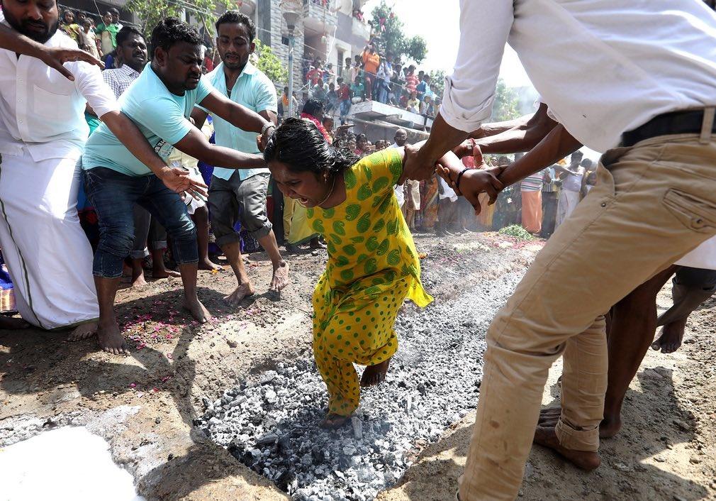عکس | کمک به زن هندی برای راه رفتن روی زغال داغ در مراسم مذهبی هندوها